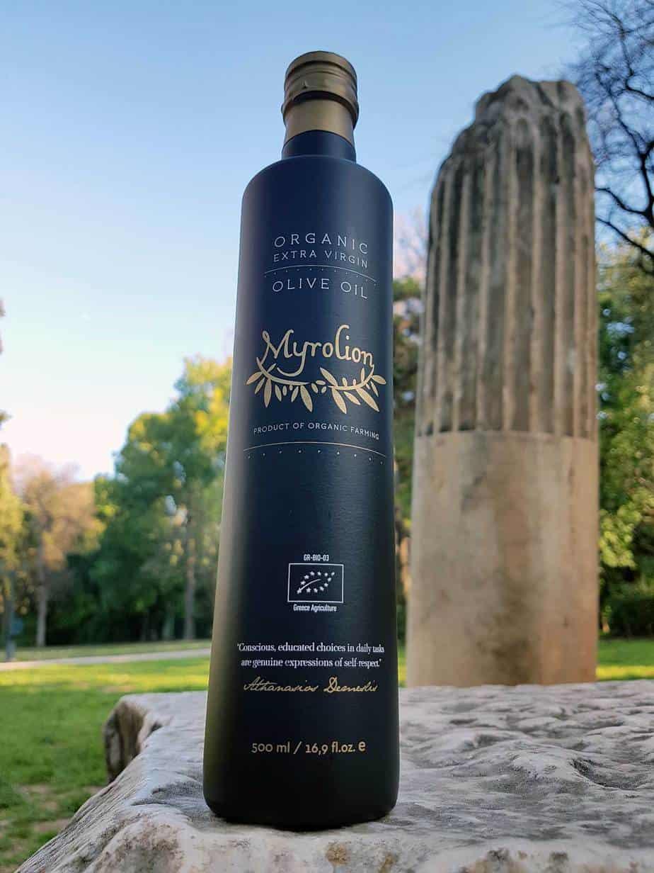 Myrolion Organic Extra Virgin Olive Oil bottle in front of ancient Greek column