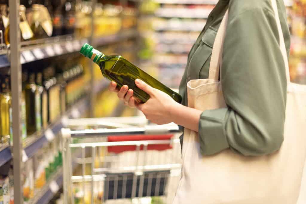 Girl choosing best olive oil in grocery store