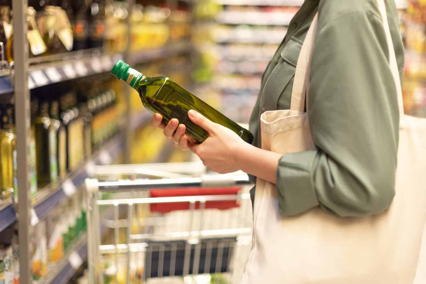 Girl choosing best olive oil in grocery store